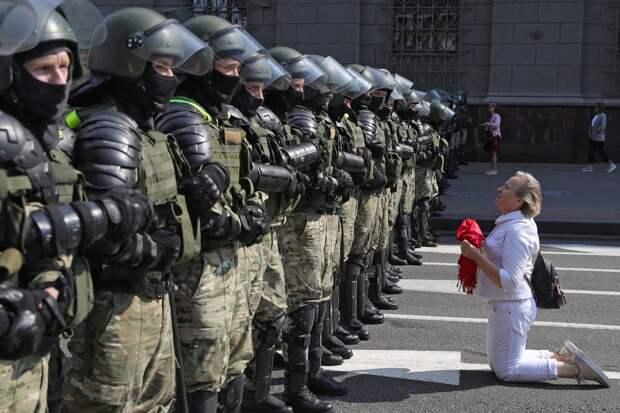 Сторонница оппозиции и военнослужащие внутренних войск Белоруссии во время акции протеста на проспекте Независимости в Минске.