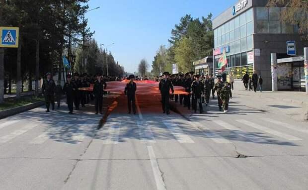 Самое большое в РФ Знамя Победы пронесли по улицам Искитима