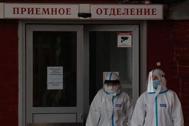 """Medical specialists wearing protective gear walk outside a hospital, amid the outbreak of the coronavirus disease (COVID-19) in Saint Petersburg, Russia November 11, 2020. The sign reads: """"Admission department"""". REUTERS/Anton Vaganov"""