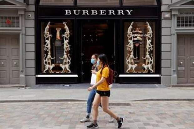 FILE PHOTO: People wearing protective masks walk past a Burberry store at Covent Garden, following the outbreak of the coronavirus disease (COVID-19) in London, Britain June 15, 2020. REUTERS/John Sibley