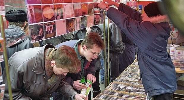 Молодые люди выбирают музыкальные диски. Один из них, с плохим зрением, аккуратно придерживает початую бутылку пива и готовится отведать жменю семян.