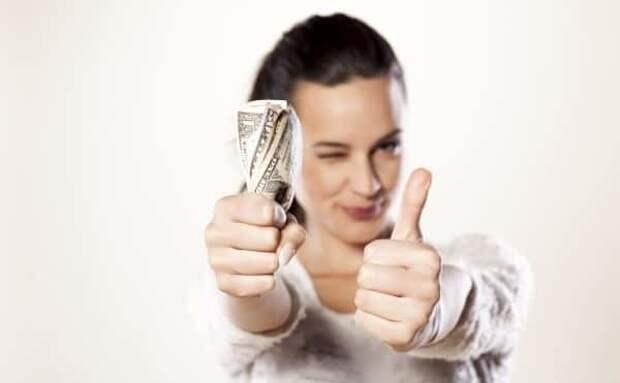 Девушка держит свернутые деньги