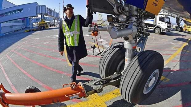 Сотрудник аэропорта проверяет самолет
