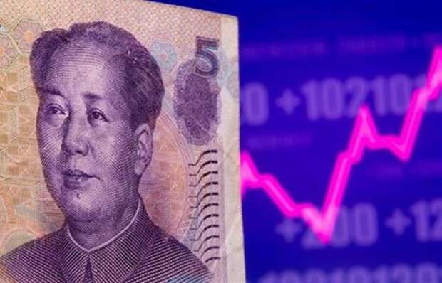 A Chinese Yuan banknote is seen in front of displayed stock graph in this illustration taken May 7, 2021. REUTERS/Dado Ruvic/Illustration