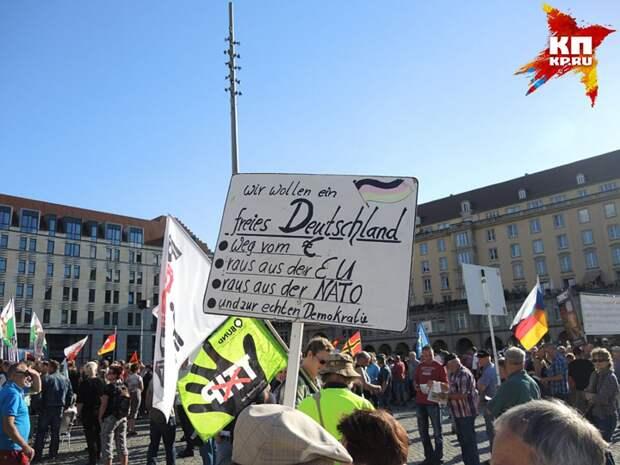 """Плакат """"Мы хотим свободную Германию: без евро, без ЕС, без НАТО и с настоящей демократией"""". Фото: Дарья АСЛАМОВА"""