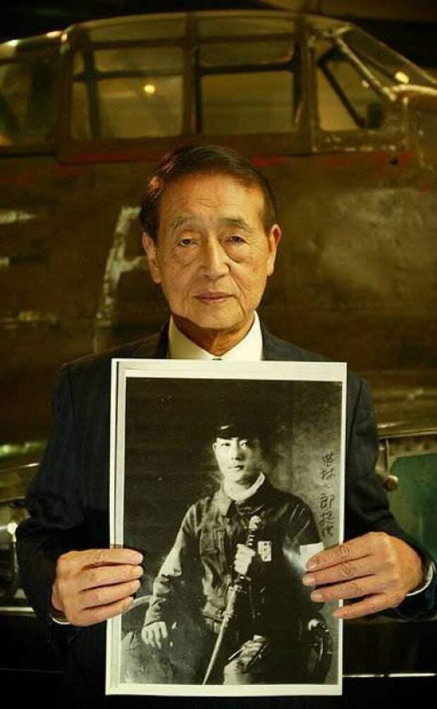 """Бывший японский пилот-камикадзе Хичиро Наемура (Hichiro Naemura) держит в руках свой портрет военных лет, стоя возле истребителя """"Mitsubishi A6M Zero"""" история, события, фото"""