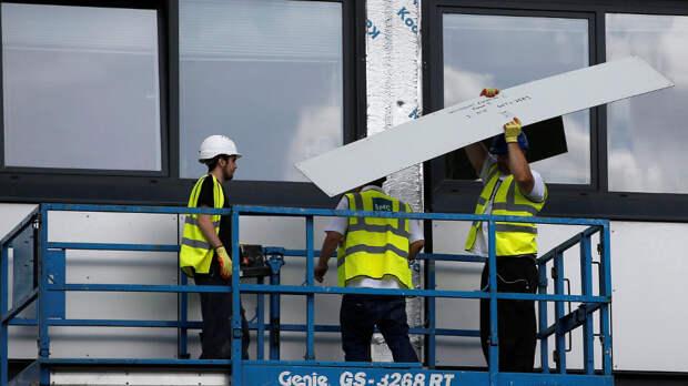 Рабочие заменяют облицовочные панели на муниципальном жилье