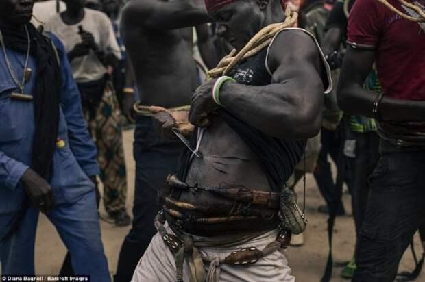 Мужчина демонстрирует физическую силу и силу духа, нанося себе порезы. Вокруг его тела обернуты защитные амулеты.