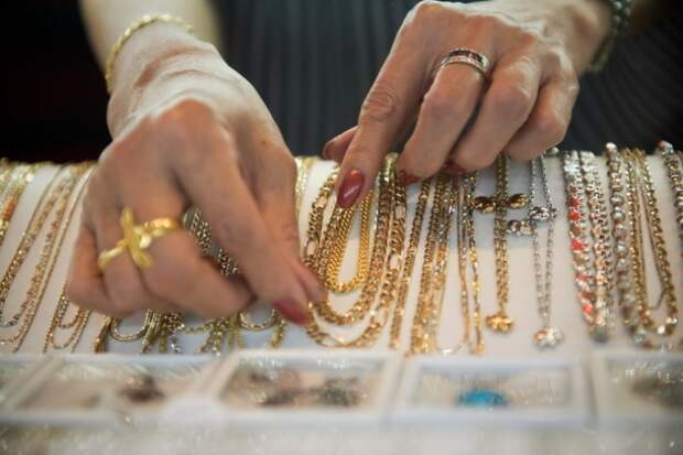 A worker shows gold necklaces in a gold jewellery shop in Bangkok on 17 April, 2013. Gold prices clawed back some losses on April 16 after suffering their heaviest slump in 30 years owing to weak Chinese growth data and reports that Cyprus was planning to sell some of its reserves of the precious metal. AFP PHOTO / Nicolas ASFOURI (Photo credit should read NICOLAS ASFOURI/AFP/Getty Images)