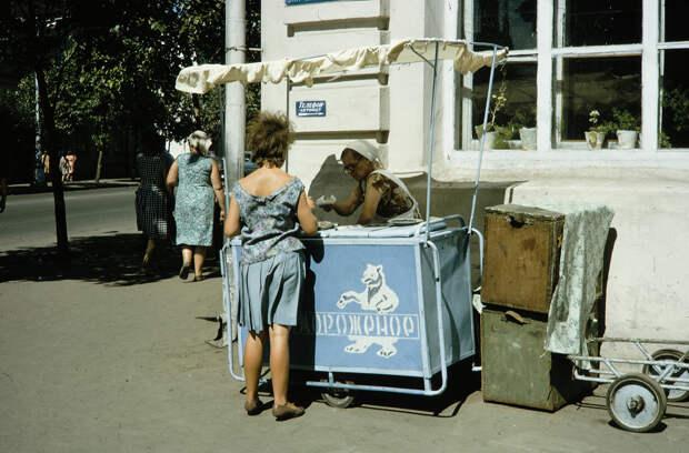 Russia, woman purchasing item from street vendor. Siberia