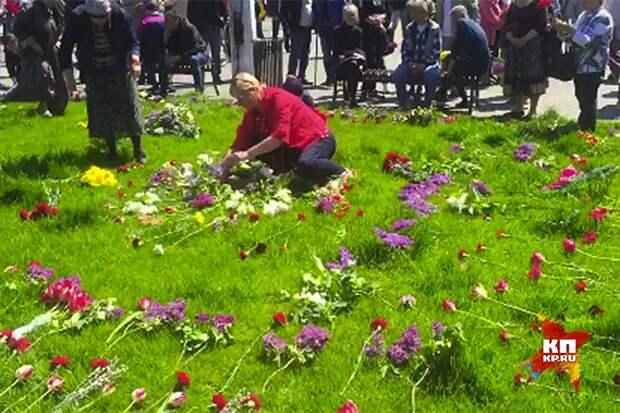 Когда пришедшие помянуть погибших поняли, что к месту гибели людей их не пропустят, они разложили цветы на близлежащей лужайке.Фото: Владимир ВОЛОШИН