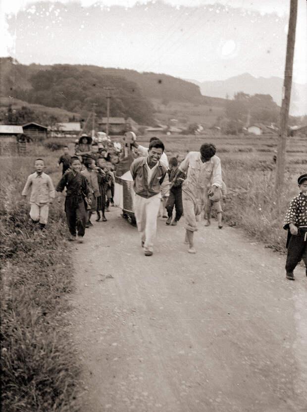 People Pulling 1930s Glider Down Dirt Road in Japan