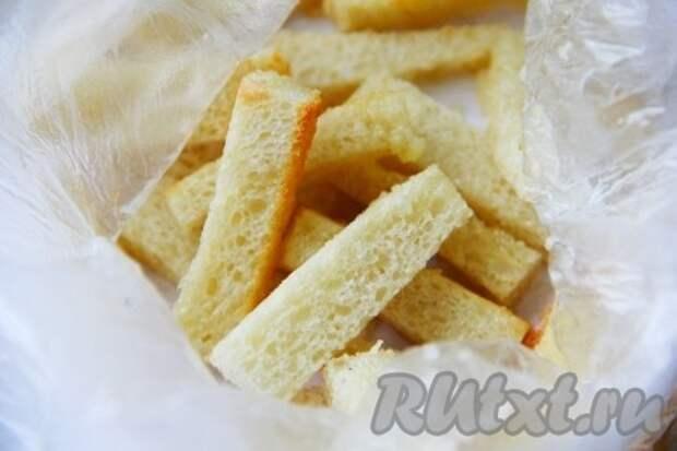 Хлеб нарезать длинными брусочками и подсушить в духовке. В отдельной миске смешать выдавленный чеснок и растительное масло. Смешать полученное чесночное масло с сухариками.