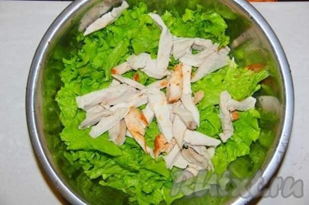 Листья салата нарвать и выложить в миску. Куриную грудку отварить и нарезать длинными полосками.