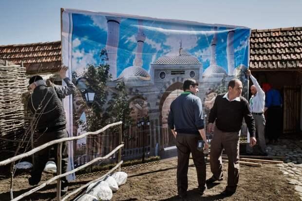 Люди устанавливают стенд на фестивеле культуры близ Шали, апрель 2015 года.