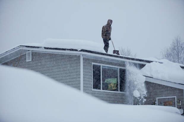 Человек очищает снег с крыши