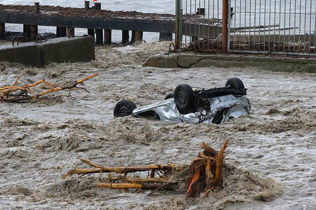На фото: автомобиль, вынесенный потоком воды на городскую набережную. Река Водопадная вышла из берегов после продолжительных дождей в Ялте.