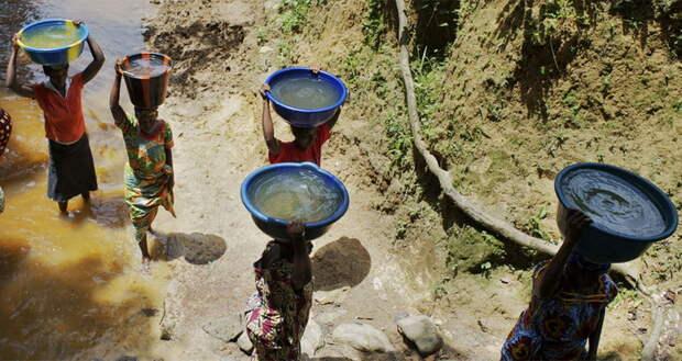Женщины носят мутную воду из реки