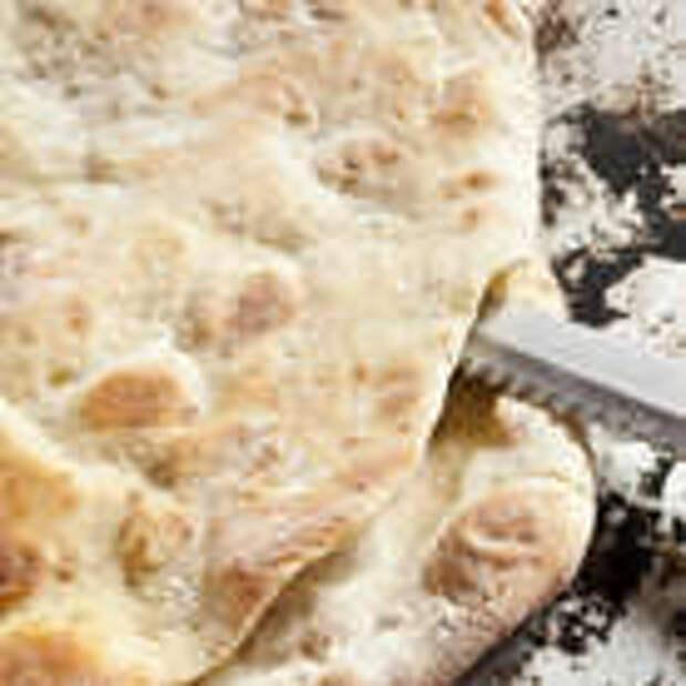Выложить на смазанный оливковым маслом противень и выпекать 10 минут в разогретой духовке. Пропеченную фокаччу разрезать вдоль пополам.