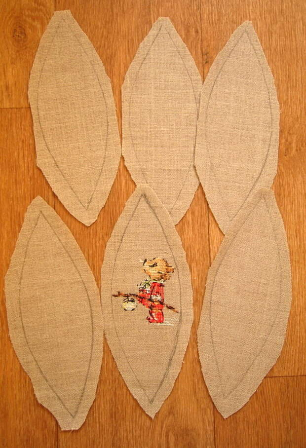 вырезанные из льна сегменты шара на одном выполнена вышивка крестом