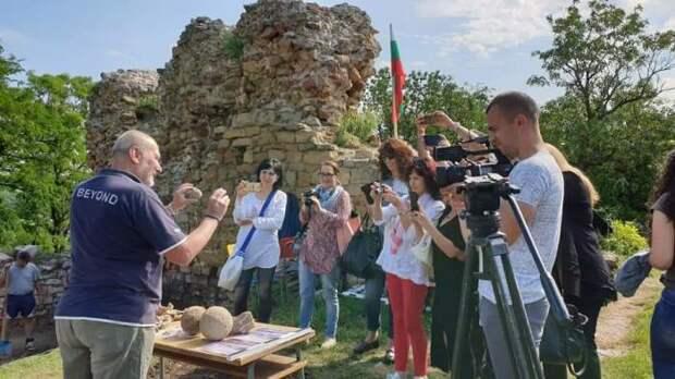 Археолог знакомит туристов с найденными артефактами.