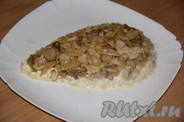 Грибы откидываем на дуршлаг и даём стечь жидкости. Выкладываем грибы поверх картофеля.