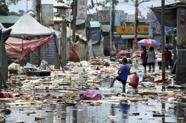 12. Мальчик пытается не столкнуться с потоком мусора, несущимся по затопленной улице в округе Шаньтоу провинции Гуандун загрязнение, китай, экология