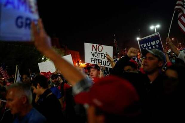 Supporters of U.S. President Donald Trump hold signs as they gather in front of the Maricopa County Tabulation and Election Center (MCTEC) to protest about the early results of the 2020 presidential election, in Phoenix, Arizona November 4, 2020. REUTERS/Edgard Garrido