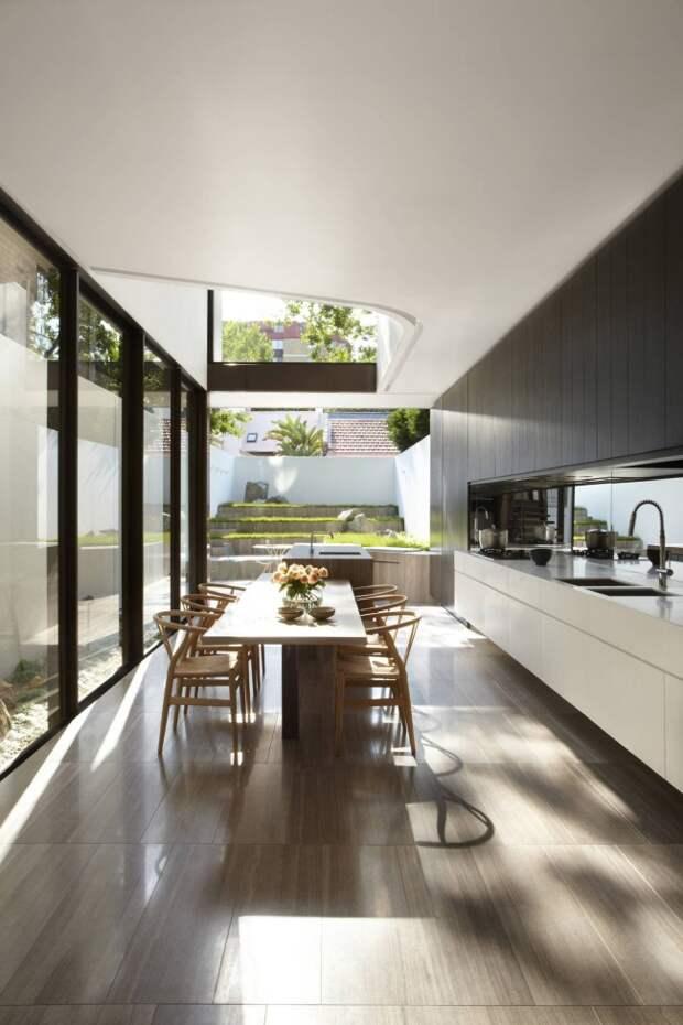 Очень просторная кухня-студия в частном доме с темным венге в оформлении рабочей зоны и светлым - в обеденной