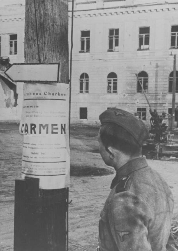 Солдат СС читает театральную афишу на улице оккупированного Харькова