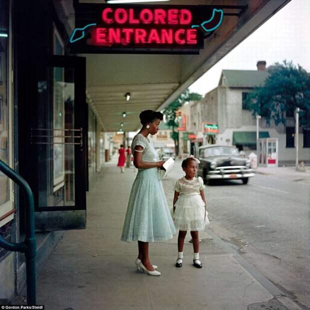 Молодая афро-американка с дочерью под указателем с надписью Вход для цветных
