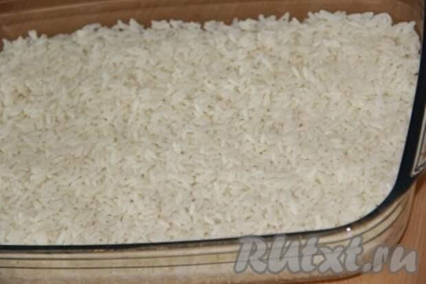 В жаропрочную форму выложить рис и разровнять.