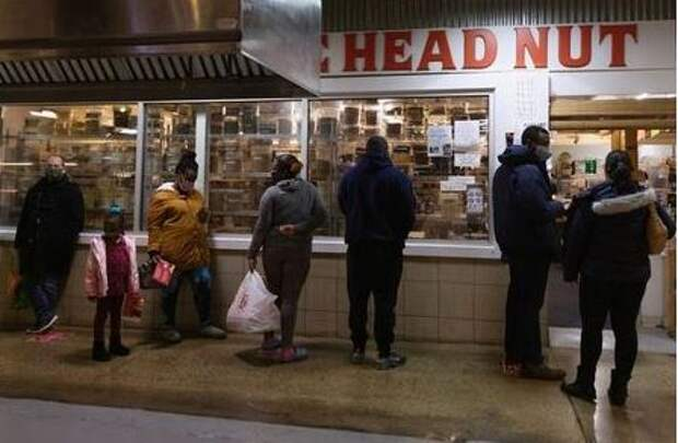 Customers wait in line to shop at a store at Reading Terminal Market amid the coronavirus disease (COVID-19) pandemic in Philadelphia, Pennsylvania, U.S., February 6, 2021. REUTERS/Hannah Beierr