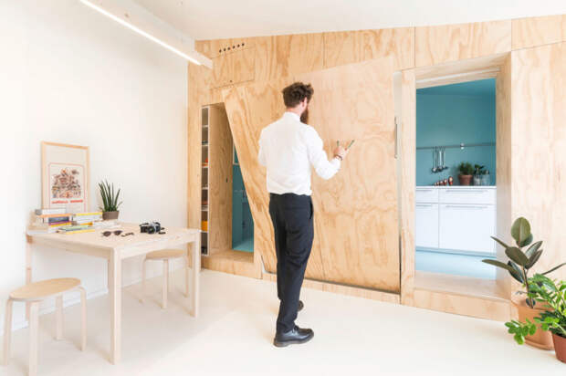 Интерьер гостиной, стены которой отделаны панелями из фанеры и кухня бирюзового цвета