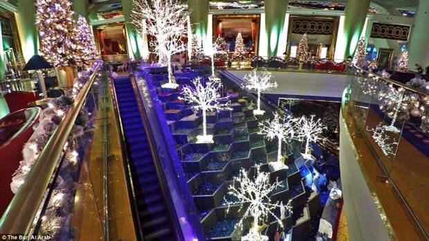 Здание фешенебельного отеля Burj Al Arab располагается на солнечном побережье в Дубае, но в самой гостинице царит настоящая зимняя сказка.