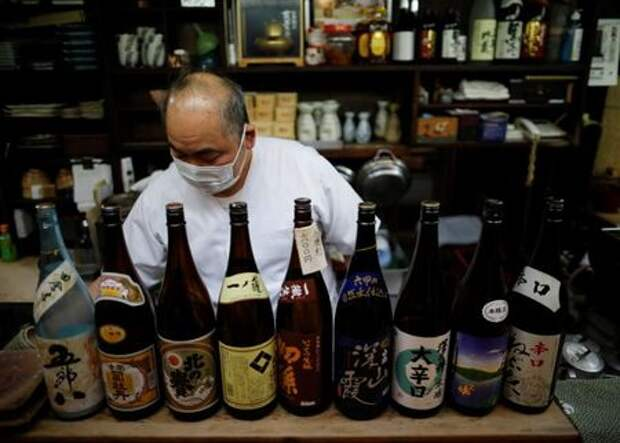 The chef of an izakaya, a Japanese-style dining bar, prepares to close around 20:00 local time next to sake bottles, amid the coronavirus disease (COVID-19) outbreak, in Tokyo, Japan February 2, 2021. REUTERS/Issei Kato