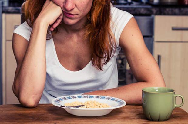 девушка сидит над тарелкой с кашей