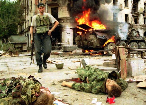 Чеченский боевик проходит мимо тел русских солдат, погибших в уличных боях в Грозном в понедельник, 12 августа, 1996. / AP / Robert King