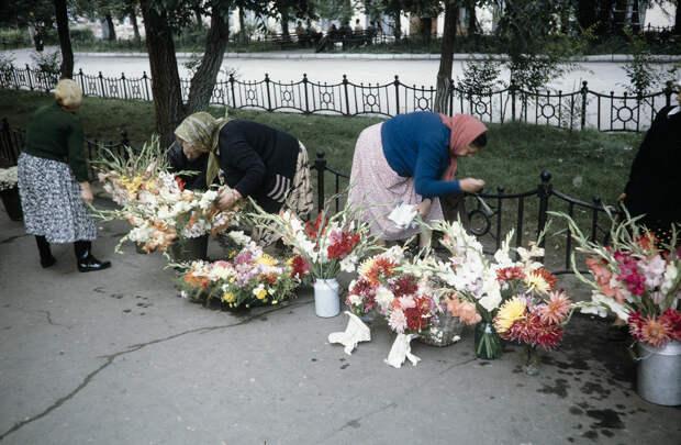 Russia, women selling flowers on sidewalk in Khabarovsk