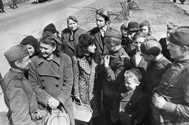 Советские бойцы беседуют с жителями Берлина на улицах города.