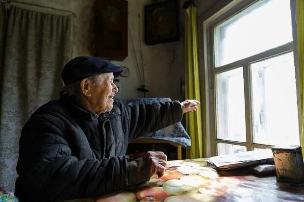 Евгений Васильевич Попов, дома сидя у окна, показывает в даль: «Вооот там, вниз по реке - деревня Гам». В ту деревню в социально-реабилитационный центр для несовершеннолетних он отдал свой капитал Фото: Наталия БЕШКАРЕВА