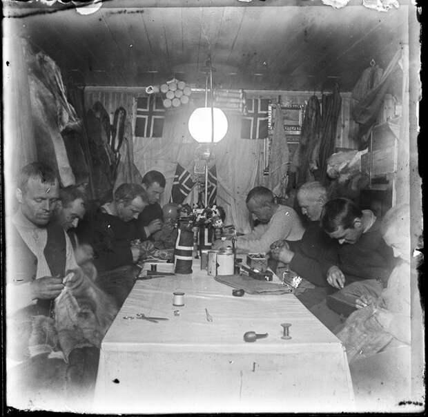 Команда Амундсена занимается подгонкой одежды во «Фрамхейме» полярной зимой 1911 года. Амундсен — первый справа, рядом с ним Ялмар Йохансен, 1911 год (Wikimedia)