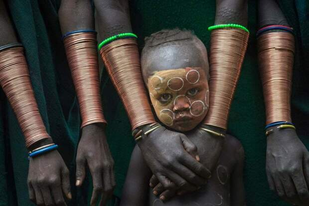 Кибиш, Эфиопия: мальчик из племени сури, живущий в эфиопской долине Омо, с женщинами из племени в длинных медных браслетах. Фотография: Дэнни Йе Син Вонг.