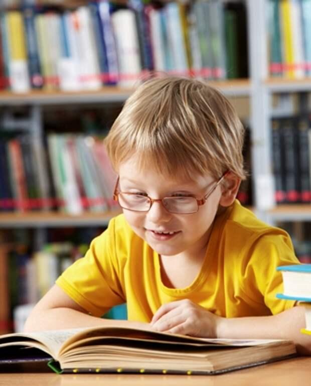 маленький мальчик читает книгу в библиотеке (фотография) - - PressFoto