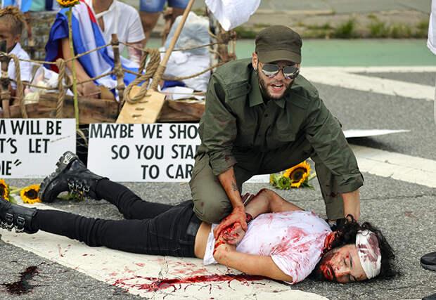 На фото: группа молодых людей из фонда «Художники вносят изменения» провела акцию, демонстрирующую военную тактику Кубы, чтобы остановить народ от протестов. Лос-Анджелес, США.