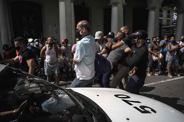 На фото: полиция задерживает антиправительственного демонстранта во время акции протеста в Гаване, Куба.