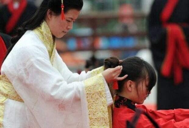 Женщина закалывает волосы девочке
