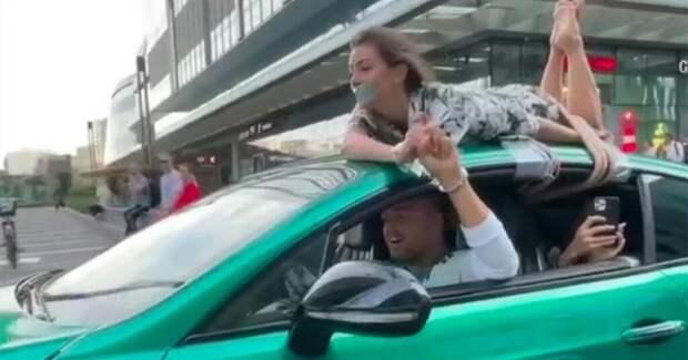 Блогер привязал свою девушку к крыше машины и проехался с ней по «Москва-Сити». ГИБДД начала проверку