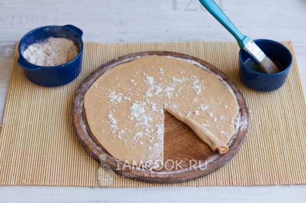 Смазать тесто маслом и посыпать мукой