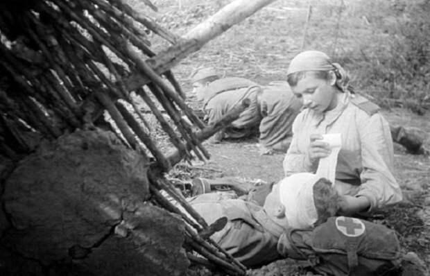 Санинструктор 705-го стрелкового полка старший сержант Пономарева перевязывает раненого в голову младшего лейтенанта  Смирнова, 1943 год.